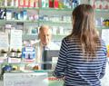 Un farmacista con la locandina che presenta i nuovi servizi offerti in accordo con l'AUSL