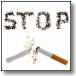 """Immagine di sigaretta spezzata con la scritta """"STOP"""" fatta con la cenere"""