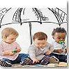 Fotografia di tre piccoli bambini seduti sotto ad un ombrello disegnato