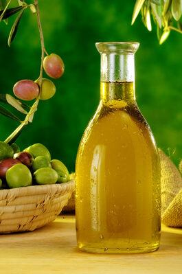 Fotografia di una bottiglia di olio riposta sul piano di un tavolo e al suo finaco un cestino con rametti di olive