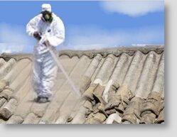 Fotografia di un uomo con tuta protettiva che sta bonificando un tetto di amianto