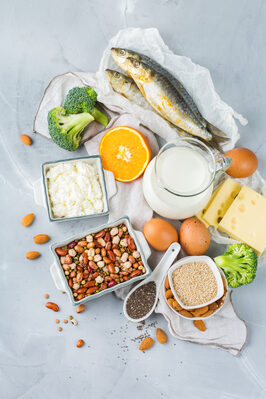 fotografia di tante ciottole viste dall'alto ripiene di yogurt, latte, semi di sesamo, semi di kia e uova, broccoli, arancia tagliata, groviera, sgombro.